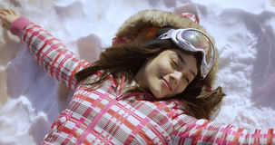 Young woman lying on snow with ski goggles Royalty Free Stock Photo