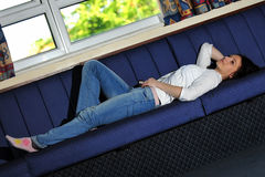 Young woman lying on the sofa. Young woman lying on the blue sofa by the window, relaxing Stock Photography