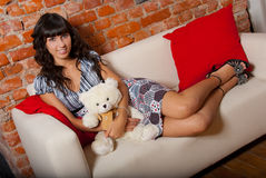 Young woman lying on a sofa Stock Images