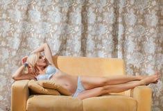 Young woman lying on sofa Royalty Free Stock Image