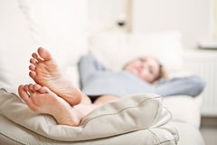 Young woman lying on sofa, focus on her feet. Barefoot young woman lying on sofa, shallow depth of field, focus on foot soles Stock Image