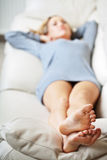 Young woman lying on sofa, focus on her feet Stock Photography