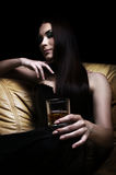 Young woman lying on sofa with a glass of whisky Stock Image