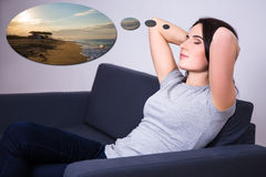 Young woman lying on sofa at home and dreaming about summer Royalty Free Stock Images