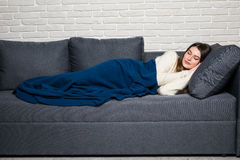 Young woman lying on sofa at home, sleeping covered with warm blanket at home Stock Photo