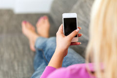 Young woman lying on sofa with mobile phone Stock Photo