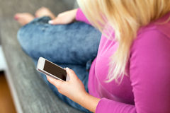 Young woman lying on sofa with mobile phone Stock Image