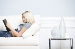 Young Woman Lying on Sofa Reading Book Royalty Free Stock Images