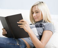 Young Woman Lying on Sofa Reading Book Royalty Free Stock Photo