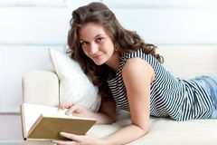 Young woman is lying on the sofa Royalty Free Stock Photos