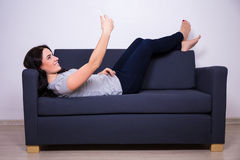 Young woman lying on sofa and taking selfie photo with mobile ph Royalty Free Stock Image