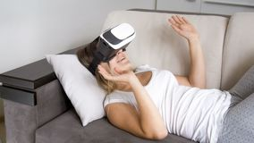Happy young woman lying on sofa and using virtual reality headset Stock Images