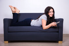 Young woman lying on sofa and watching tv at home. Young beautiful woman lying on sofa and watching tv at home Stock Image
