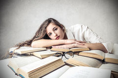 Young woman lying on some books Royalty Free Stock Image