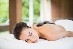 Young woman lying with spa stones at her back. Young woman lying on massage table with spa stones at her back Stock Image