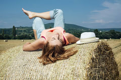 Young woman lying on a stack of straw and enjoying the sunshine Stock Image
