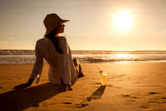 Young woman lying in straw hat in sunglasses on beach Stock Photos
