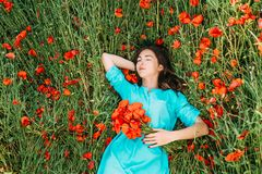 Young woman lying on summer poppy meadow. Beautiful brunette young woman lying and relaxing on summer poppy flowers meadow royalty free stock photo
