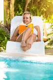 Young woman lying in a sunbed  and reading a book Royalty Free Stock Photo