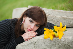 Young woman lying on the tombstone. Sad young woman with a lilies lying on the tombstone Royalty Free Stock Photo