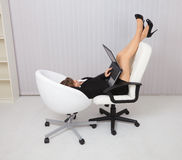 Young woman lying in two chairs with laptop Stock Photos