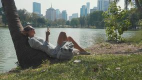 Young woman lying under palm tree using mobile phone in a park. Girl relaxing at city park with lake and skyscrapers on the background. Break of megapolis life stock footage