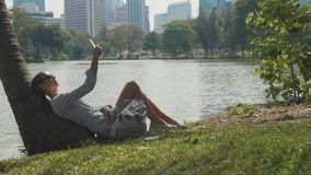 Young woman lying under palm tree using mobile phone in a park. Girl relaxing at city park with lake and skyscrapers on the background. Break of megapolis life stock video footage