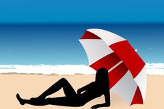 Young woman lying under an umbrella on the beach Royalty Free Stock Image