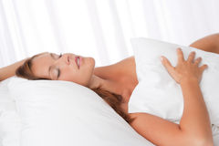 Young woman lying in white bed Royalty Free Stock Photography