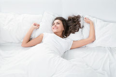 Young woman lying on the white linen in bed stock images