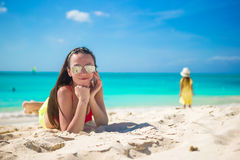 Young woman lying on white sand and talking by her Royalty Free Stock Photos