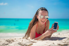 Young woman lying on white sand and talking by Stock Photography