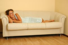 Young woman lying on the white sofa Royalty Free Stock Photos