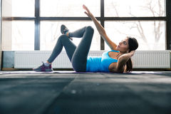 Young woman lying on the yoga mat and doing exercise Royalty Free Stock Photography