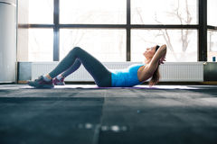 Young woman lying on the yoga mat and doing fitness exercise Royalty Free Stock Image