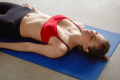 Young woman lying on a yoga mat and rest Royalty Free Stock Images