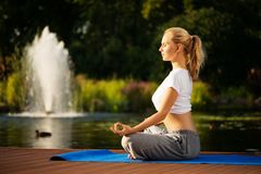 Young woman maditating in lotus pose Royalty Free Stock Photo