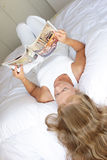 Young woman with magazine. Young woman lying on bed reading interior magazine royalty free stock photos