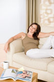 Young woman with magazine and coffee on sofa royalty free stock photos