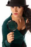 Young woman with magnifier glass and hat looking Stock Photography