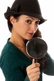 Young woman with magnifier glass and hat looking Stock Images