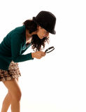 Young woman with magnifier glass and hat looking Stock Photos