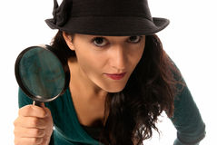Young woman with magnifier glass and hat looking Stock Image