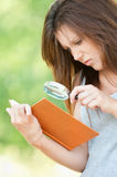 Young woman magnifier regards book. Portrait serious beautiful young woman magnifier regards book at summer green park Stock Photo