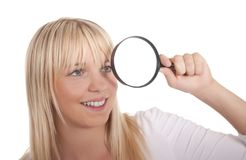 Young woman with magnifying glass Royalty Free Stock Images