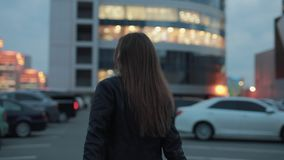 Young woman make follow me gesture in the evening city. Young woman make a follow me gesture walking in the evening city stock video