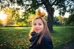 Young woman make a grimace in autumnal park Royalty Free Stock Photo