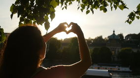 Young Woman make hearth symbol in sunset. Woman make hearth symbol in sunset stock video