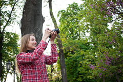 Young woman make photo of spring flowers on DSL camera Stock Photography