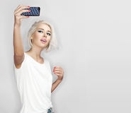 Young woman make selfie. Blonde woman is photographed on a white background Stock Images